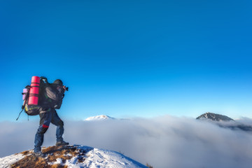 Photographer takes pictures on top of the mountain in winter