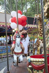 Bride with balloons rides on the carousel