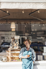 Coffee roaster holding cup in front of his his shop