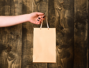 light orange shopping bag in female hand on wooden background