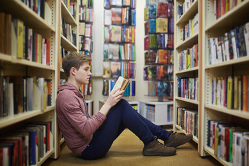 Concentrated guy reading book in library