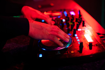 hands DJ music mixer on the party in the night club