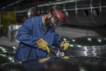 Factory worker operating steel cutter