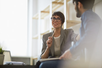 Two cheerful colleagues smiling while discussing something in modern office, focus on stylish businesswoman wearing creative haircut and glasses