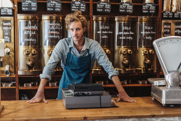 Portrait of coffee roaster at counter in his shop