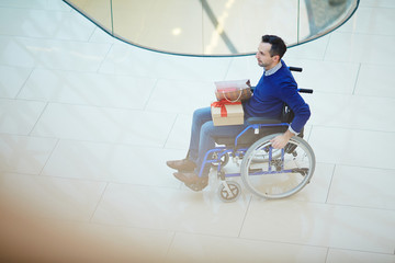 Disabled consumer in wheelchair looking for gifts in the mall