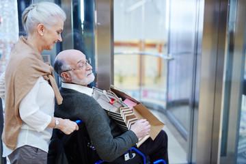 Senior spouses entering modern shopping-center