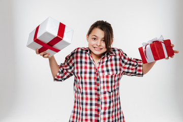 Cheerful young girl posing with two gifts