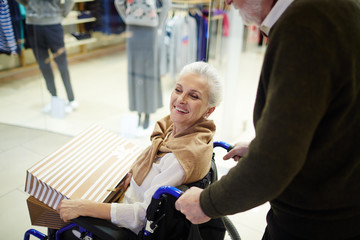 Happy disabled woman talking to her caregiver during shopping