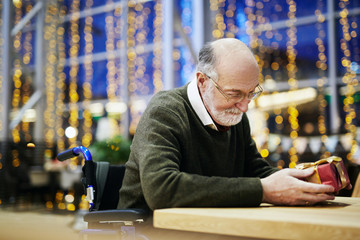 Grey-haired man in wheelchair looking at gift in his hands