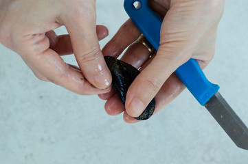 Young woman hands opening fresh mussel shell with a knife