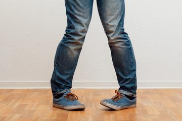 Mann steht in X-Bein Haltung vor einer Wand, untere Körperhälfte