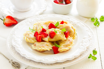 Traditional homemade dumplings with strawberries and cream.