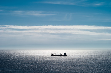 Small freight ship shows as a silhouette in bright sun. West Cape, Stad, Norway