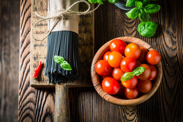 Black spaghetti with tomatoes, basil and hot chili peppers