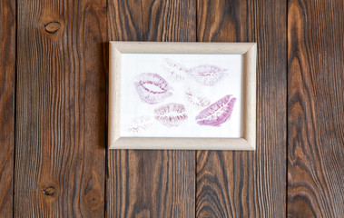 traces of lipstick kisses on a white paper in a frame. Dark wood