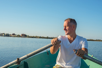Smiling man is rowing on a small boat in a calm sea