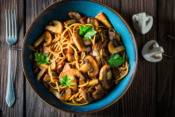 Creamy spaghetti with mushrooms and parsley in blue bowl