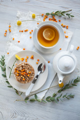 Serving table for breakfast: tea with lemon, granola and tea pot.