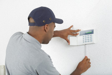 Workman fitting alarm key pad to wall