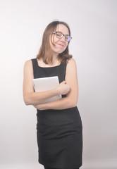 Девушка в чёрном платье в очках и белым планшетом в руках улыбается
