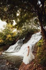 Beautiful stylish bride posing near the waterfall outside