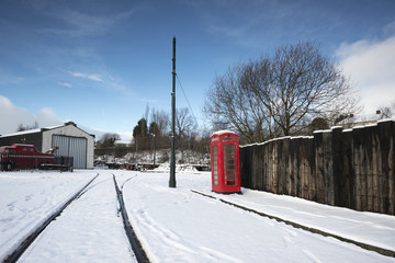 Red telephone box and tramlines in the snow.