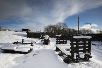 Winter snow scene featuring old broken wagons and machinery.