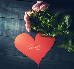 Bouquet of roses with paper heart on a blue wooden background.