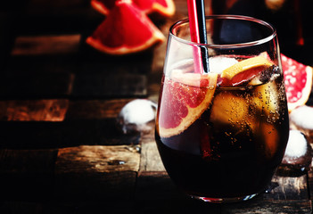 Alcoholic cocktail with cola, juice and ice, dark wood backgroun