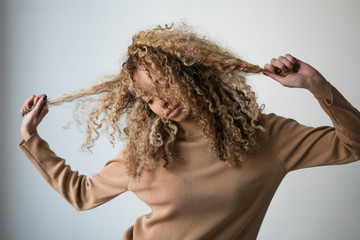 Young woman tugging on her curly hair