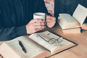 a man holding a cup of coffee with a pen and glasses on text boo