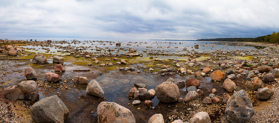 Baltic sea coast with granite boulders in cloudy day. Relaxing and cold landscape, wide panoramic view.