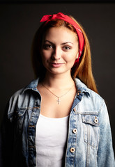 Girl with red hair in jean jacket on black background