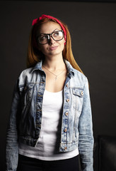 Girl with red hair in glasses on black background