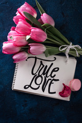 Fresh pink tulip flowers bouquet . with inscription true love on paper. Spring holiday concept