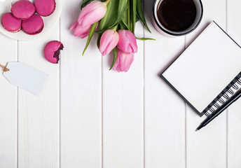 Pink tulips, macarons, empty notepad and coffee on white wooden
