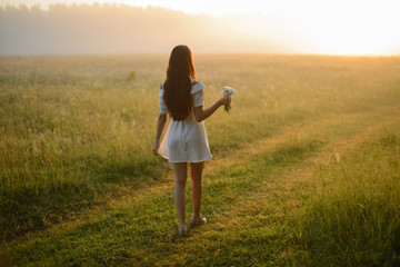 beautiful sexy girl model in white dress and long hair with flowers of camomile goes toward dawn, back
