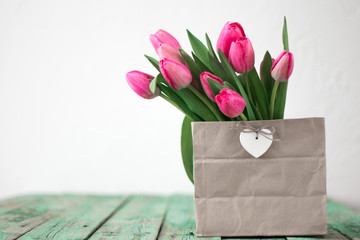Fresh pink tulip flowers bouquet on shelf in front of swall. View with copy space