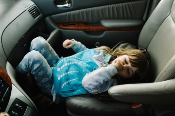 Young girl in car, lying in passenger seat, sucking thumb