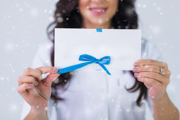 Close up of doctor holding blank white gift card over gray background and snow