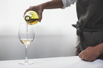 Close-up of woman pouring white wine in wine glass