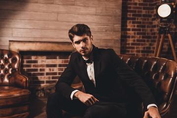 Portrait of handsome businessman in elegant black suit sitting o