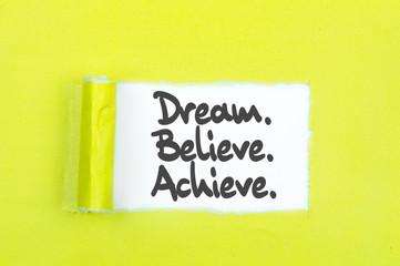 Dream, Believe, Achieve. Words written under torn paper. Motivation concept text.