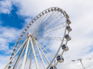 A Ferris wheel with vivid blue sky background, photographed outdoor with a wide angle lens.