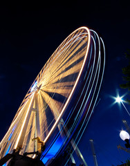 A vibrant Ferris wheel with vivid colours, photographed outdoor with long exposure at twilight. Slow shuts speed motion blur.