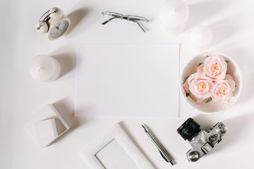 White desk with glasses, roses, candles, pen and film camera. Empty sheet in the middle. Top view, flat lay, copyspace.