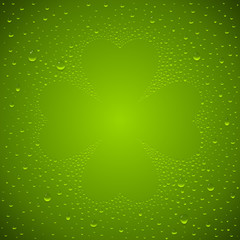 St. Patricks's day wet bottle background. A clover leaf on a green glass surface. Shamrock symbol composed of water droplets.