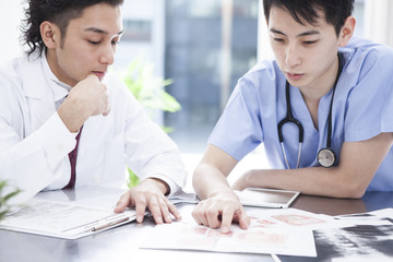 Two doctors are discussing treatment policy in the examination room