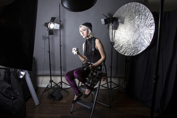 Female professional photographer dressed like a hipster or a millennial drinking coffee and taking a break.  She is resting inside a photography studio thinking to be creative and artistic.